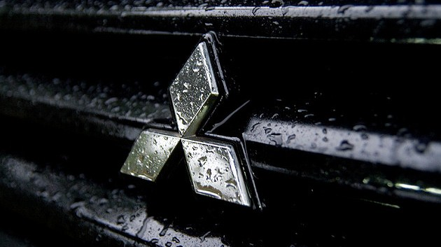 Mitsubishi logo on the wet car