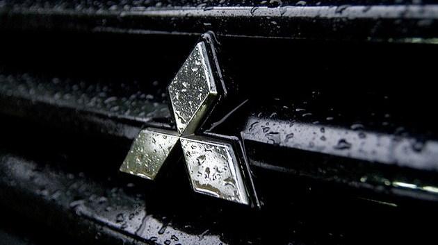 Mitsubishi logo on the wet car